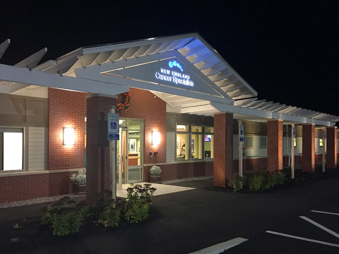 Color photo taken at night of front entrance at New England Cancer Specialists, West Kennebunk, Maine